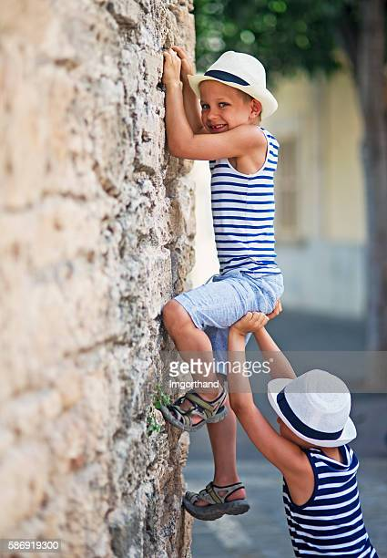 Little naughty tourists climbing ancient wall