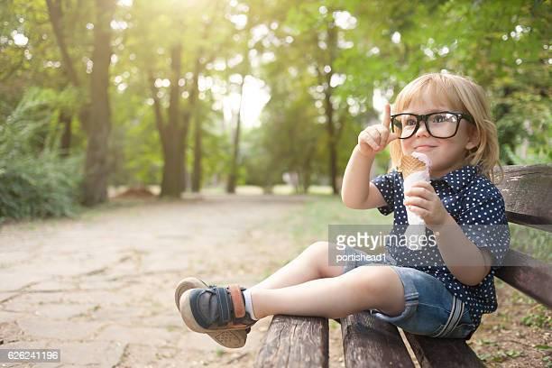 Little nerd boy with eyeglasses eating icecream in park