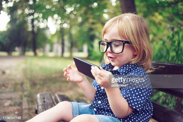 little nerd boy with eyeglasses using smart phone - portability stock pictures, royalty-free photos & images