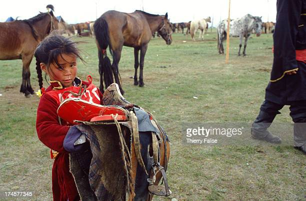 Little Nergui 6 yearsold brings her saddle to the horse before the start of the horserace during the Naadam festival Naadam is the national sports...