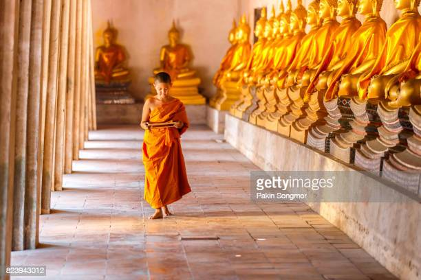 Little novice monk hand holding blackboard and walking in old temple, Ayutthaya Province, Thailand.