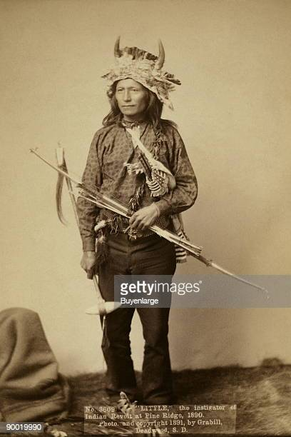 Little, Oglala band leader, full-length studio portrait, standing, facing front, wearing horn headdress, pants and shirt, and holding bow, arrows and...