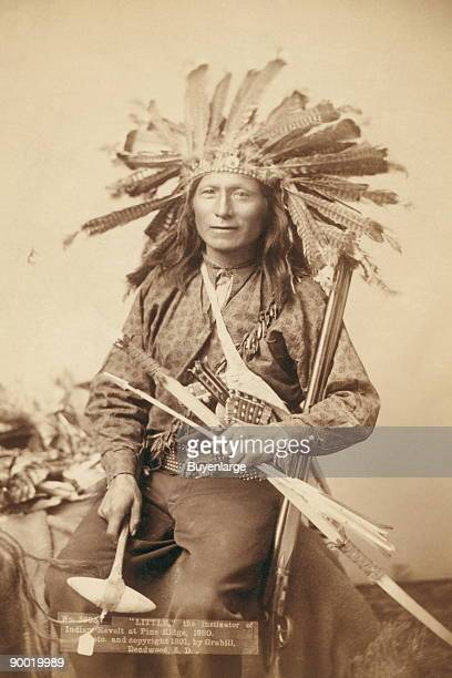 Little Oglala band leader threequarter length studio portrait seated wearing a turkey feather headdress and holding various weapons