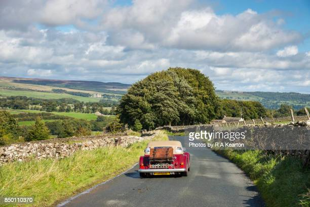 Little old vintage car exploring the country roads of Wensleydale, North Yorkshire, England