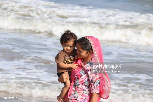 little one years old boy portraits with mother in summer afternoon on beach chennai, marina beach - 25 29 years stock pictures, royalty-free photos & images