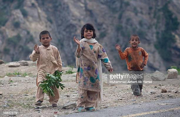 CONTENT] 3 little pathan children waving their hands as our coaster passed through them in Naran hilly area
