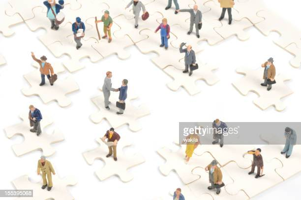 Little people on puzzle pieces shaking hands and isolated