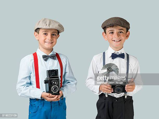 little photographers holding old fashioned cameras - サスペンダー ストックフォトと画像