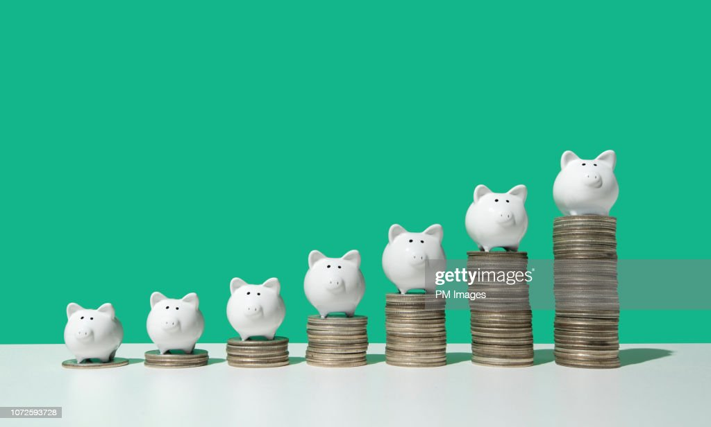 Little piggy banks on ascending stacks of coins : Stock-Foto