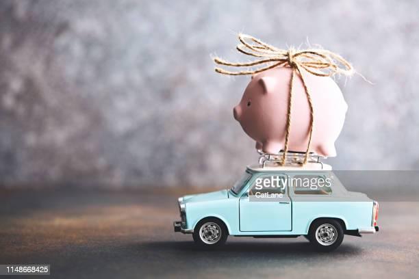kleines rosafarbenes sparschwein an die spitze eines alten autos gebunden - sparschwein stock-fotos und bilder