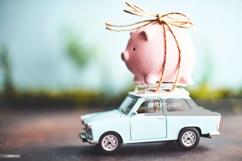 Little pink piggy bank tied to the top of an old car : Stock Photo