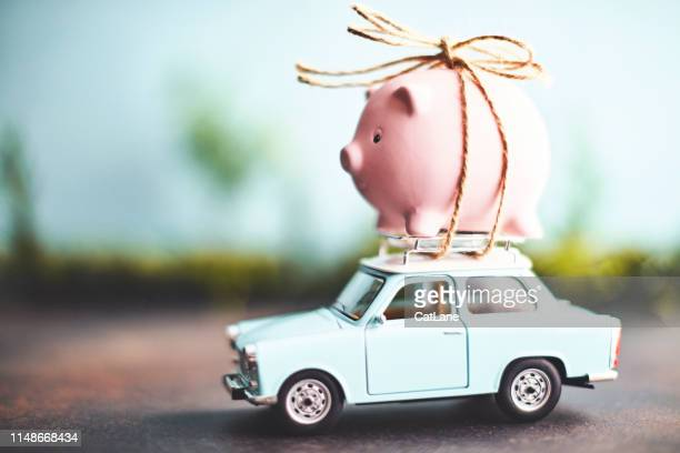little pink piggy bank tied to the top of an old car - finanza foto e immagini stock