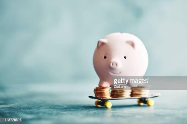 little pink piggy rijden op een skateboard met geld - geld stockfoto's en -beelden