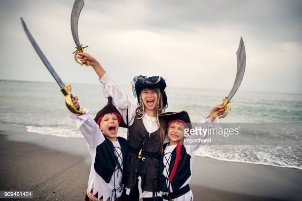 little pirates cheering on beach - female pirate stock photos and pictures