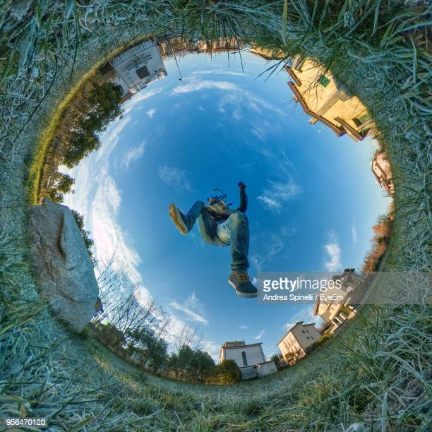 little planet format of man jumping against sky - little planet format stock photos and pictures