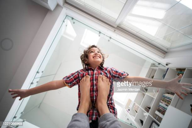 little playful boy flying on his father's legs - unusual angle stock pictures, royalty-free photos & images