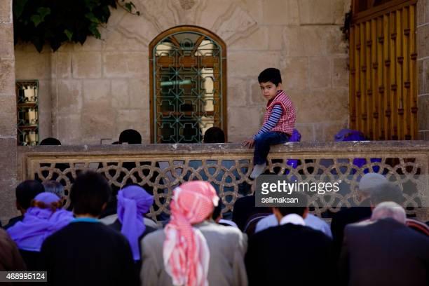 Poco allegro ragazzo seduto tra di pregare persone a venerdì