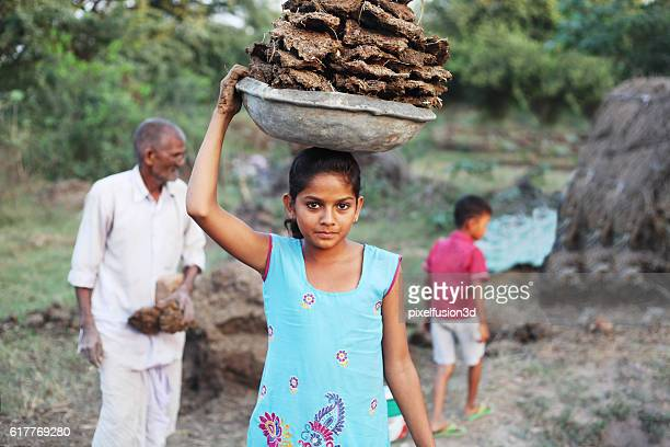 little poor girl carrying dung cakes - salwar kameez stock photos and pictures