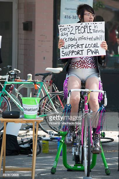 PORTUGAL TORONTO ONTARIO CANADA Little Portugal Festival Young woman pedaling a stationary bicycle holding a placard asking for donation and support...