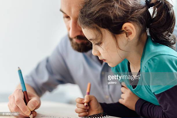 little prescholar girl and father drawing together at home