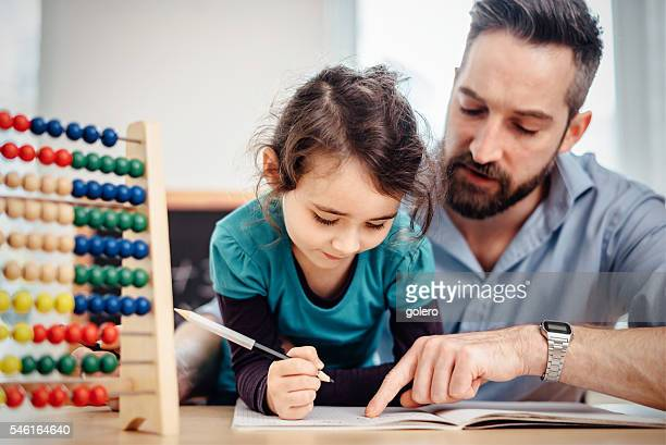 little pre-scholar girl and father learning calculating at home