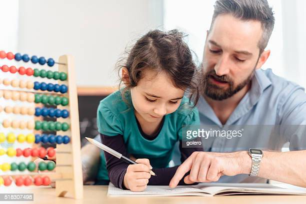 little pre-scholar girl and father learning calculating with colored balls