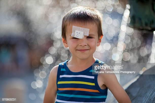 Little preschool boy with a big band aid on head