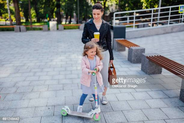 Little preschool girl is riding kick scooter in a modern urban environment
