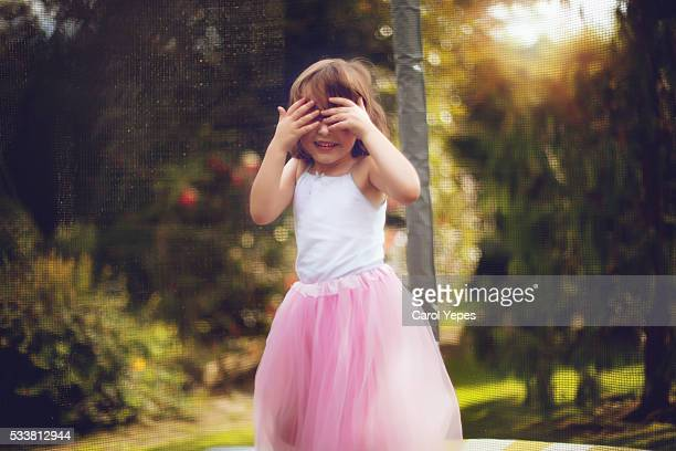 little princess with pink tutu covering face with hands