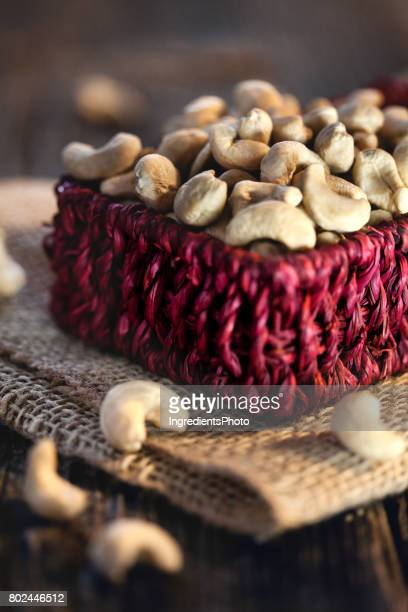 Little red basket with fresh cashew on a wooden table.