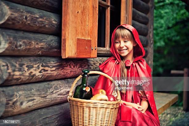 Caperucita roja en el frente de la cabaña.