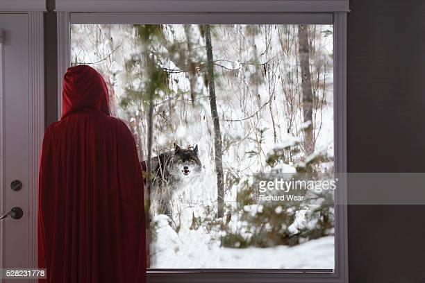 Little red riding hood looking out window at big bad wolf