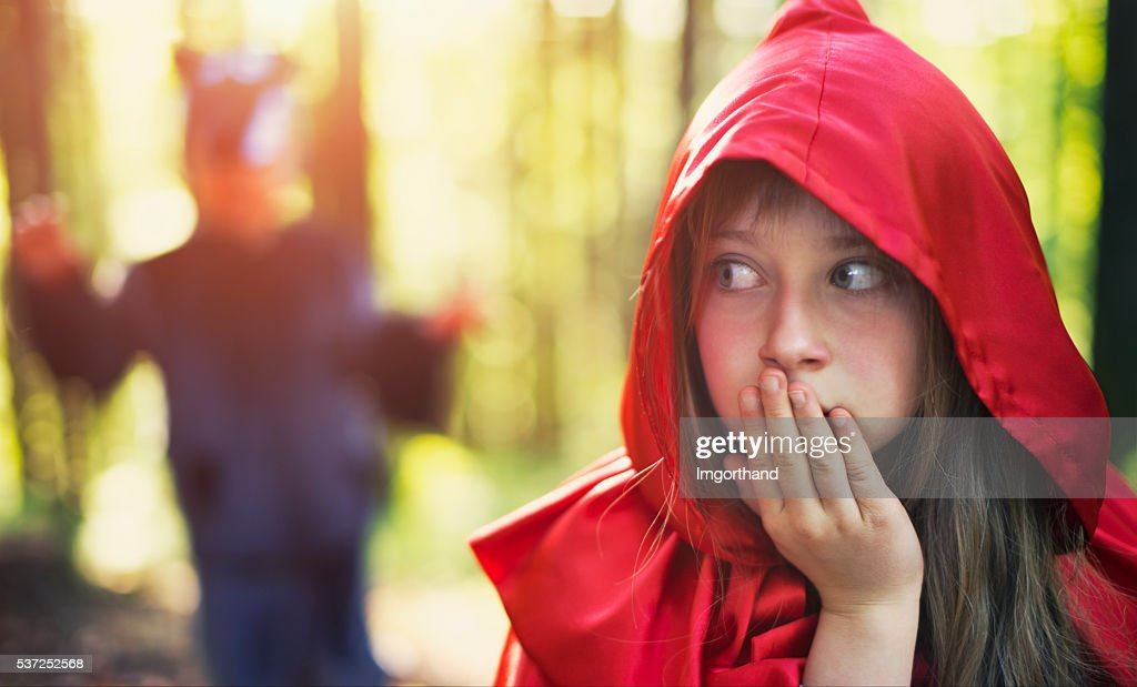 Little Red Riding Hood noticing the wolf : Stock Photo