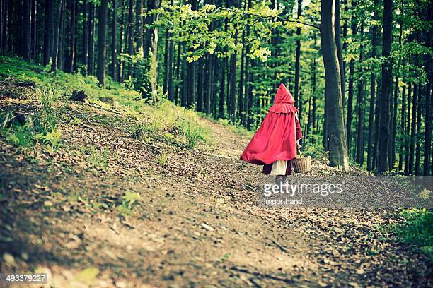 little red riding hood walking through the forest - fairytale stock pictures, royalty-free photos & images