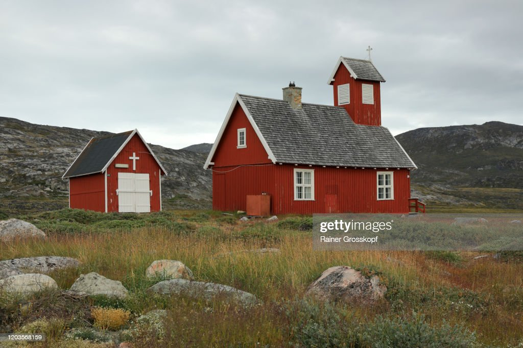 A little red wooden church in an arctic landscape with cloudy sky : Stock Photo