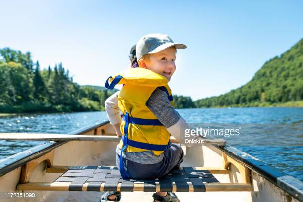 little redhead boy canoeing with his family at parc national de la jacques cartier, quebec, canada - sunny stock pictures, royalty-free photos & images