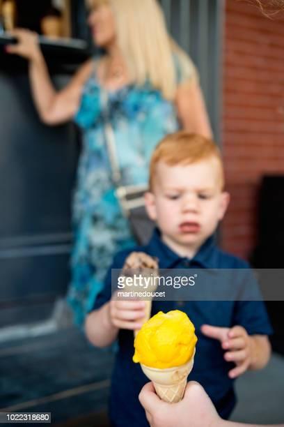 """kleine roodharige jongen buitenshuis een ijsje eten. - """"martine doucet"""" or martinedoucet stockfoto's en -beelden"""