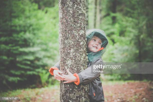 little redhead boy embracing a tree and wearing mosquito netting hat - tick bite stock pictures, royalty-free photos & images