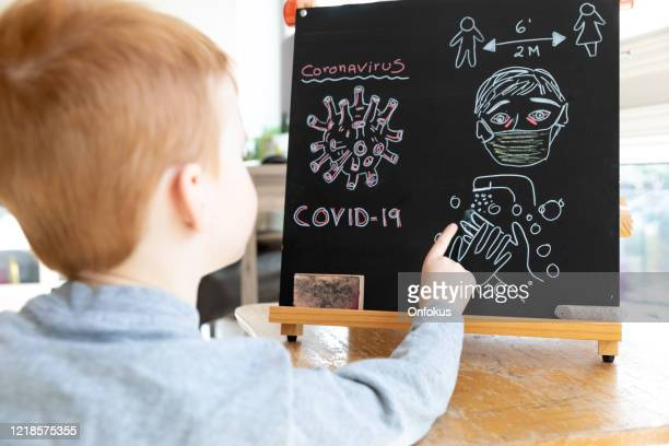 little redhead boy learning about coronavirus and covid-19 - showing respect stock pictures, royalty-free photos & images
