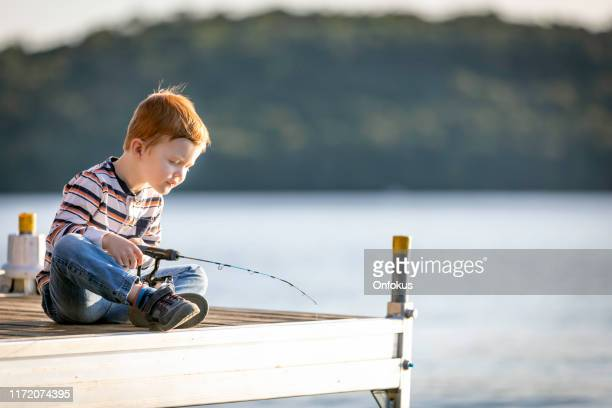 little redhead boy learning to fish at sunset in summer - first occurrence stock pictures, royalty-free photos & images