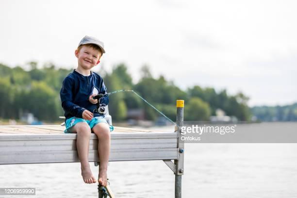 夏に魚を学ぶ小さな赤毛の少年 - 淡水釣り ストックフォトと画像