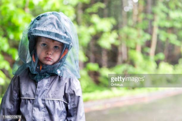 little redhead boy playing outside on campground and wearing mosquito netting hat - tick bite stock pictures, royalty-free photos & images