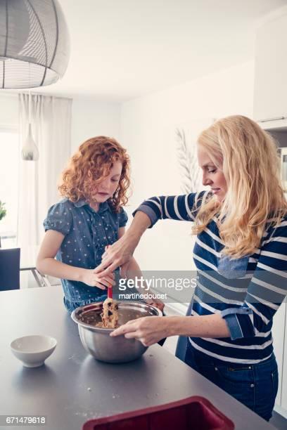 """roodharige meisje een banaan cake thuis met moeder maken. - """"martine doucet"""" or martinedoucet stockfoto's en -beelden"""