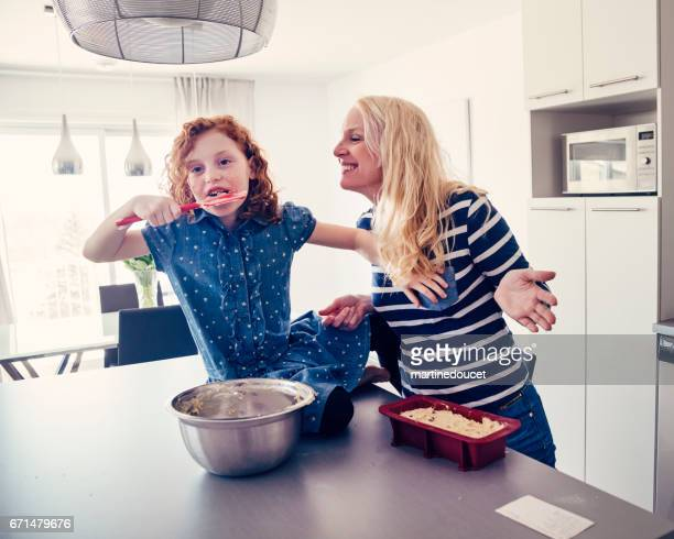 Roodharige meisje een banaan cake thuis met moeder maken.