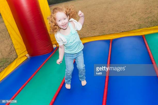 Little redheaded girl jumping in bounce house