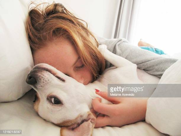 Little redheaded girl laying in bed with her white dog. She is hugging the dog and her eyes are closed. The dog is looking back at the camera and she looks like she is smiling at the camera.