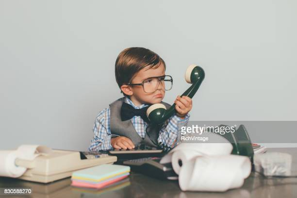 little retro business boy works the phone - fun calculator stock photos and pictures