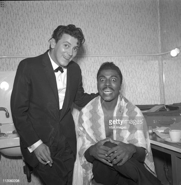 Little Richard seated with Gene Vincent posed backstage 1959