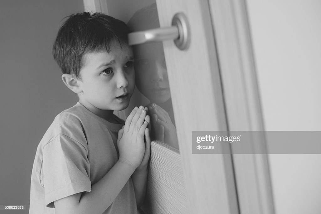 Little sad boy overhears fight of his parents - B&W : Stock Photo