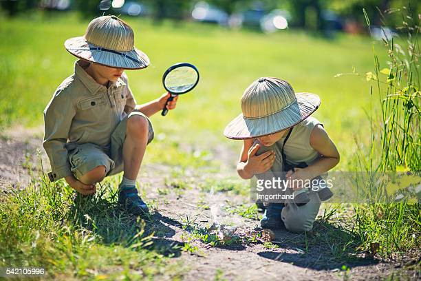 Little safari boys making fire with magnification glass